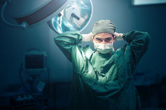 Male surgeon tying face mask at operating room. Male surgeon tying mask at operating room Stock Photos