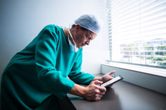 Male surgeon using digital tablet. Of hospital Stock Image