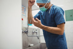 Male surgeon washing hands prior to operation using correct technique for cleanliness Stock Photo