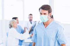 Male surgeon wearing mask with colleagues in meeting. At a medical office Royalty Free Stock Photos