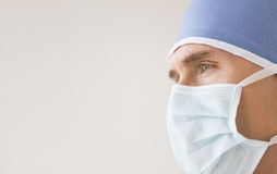 Male Surgeon Wearing Surgical Mask And Cap. Close-up of male surgeon wearing surgical mask and cap looking away against gray background Royalty Free Stock Photo