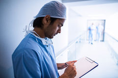 Male surgeon writing on a clipboard. At hospital Stock Photos