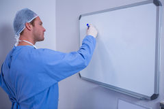 Male surgeon writing on whiteboard Royalty Free Stock Images