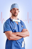 Male Surgeon. Young male surgeon with scrubs and a stethoscope, with a EKG graph behind him Royalty Free Stock Photography
