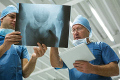 Male surgeons holding digital tablet while discussing x-ray. In hospital Stock Images
