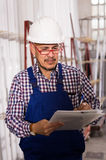 Male surveyor in coverall doing checkup and filling papers. Happy russian male surveyor in coverall doing checkup and filling papers Royalty Free Stock Image