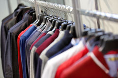 Male sweaters and jackets hanging in wardrobe.  Stock Photo