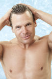 Male swim model. Portrait of muscular shirtless male swimmer getting out of water as he combs back hair with hands and smiles Stock Photos