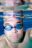 Male swimmer as seen underwater. Male, middle aged swimmer as seen underwater with blue goggles on Stock Image