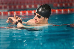 Male swimmer checking his watch. In a pool Royalty Free Stock Photo