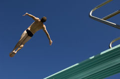 Male Swimmer Diving From Springboard. Low angle view of a male swimmer diving from springboard against the blue sky Stock Images