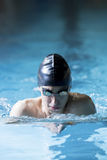 Male swimmer doing breaststroke exercise. Young male swimmer is swimming breaststroke in an indoor swimming pool - focus on the cap Stock Photos