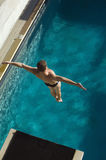 Male Swimmer Jumping From Springboard. High angle view of a male swimmer jumping from springboard into the pool Stock Photo