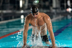 Male swimmer lifting himself out Royalty Free Stock Photo