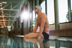 Male swimmer relaxing at the edge of a swimming pool. Side view shot of fit young male swimmer relaxing at the edge of a swimming pool Royalty Free Stock Photos