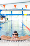 Male Swimmer resting. After several laps in the indoor swimming pool Stock Images