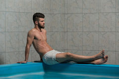 Male Swimmer Resting In Pool. Happy Attractive Man Resting Relaxed On Edge Of Swimming Pool Stock Photo
