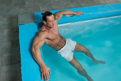 Male Swimmer Resting In Pool. Happy Attractive Muscular Mature Man Resting Relaxed On Edge Of Swimming Pool Stock Photo