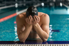 Male swimmer standing at the edge of a pool. With his head in his hands Stock Photos