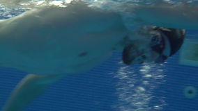 Male swimmer swimming crawl stroke in swimming pool underwater view. Close up man swimmer in black cap and goggles swims crawl stroke on swimming path in a stock footage