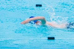 Male swimmer swimming freestyle stroke in swimming pool. Male swimmer swimming freestyle stroke in a swimming pool Royalty Free Stock Image