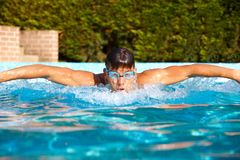 Male swimmer in swimming pool. Male swimmer in outdoor swimming pool at summer, butterfly stroke Stock Photo