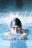 Male swimmer swimming with a swim board. Young male swimmer swimming with a swim board doing leg exercises in an indoor swimming pool - focus on the face Royalty Free Stock Image