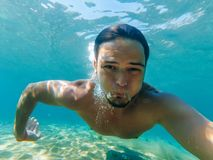 Male swimmer under water in the sea makes selfie. And let the bubbles of oxygen Royalty Free Stock Photos