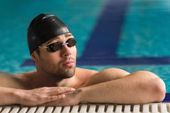 Male swimmer wearing goggles and swimming cap resting Royalty Free Stock Photography