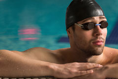 Male swimmer wearing goggles and swimming cap resting Stock Photo