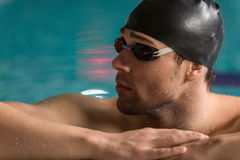 Male swimmer wearing goggles and swimming cap resting. Cropped image of a male swimmer wearing goggles and swimming cap resting on the edge of a swimming pool Stock Photography