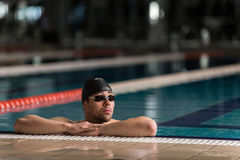 Male swimmer wearing goggles and swimming cap resting. On the edge of a swimming pool Royalty Free Stock Images