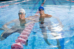 Male swimmers in swimming pool, smiling, portrait Stock Image