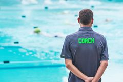 Male swimming coach standing by the swimming pool watching swimm Stock Images