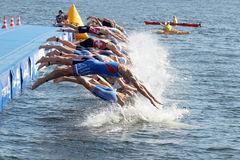 Male swimming competitors when the start signal goes. STOCKHOLM - AUG 22, 2015: Group of male swimming competitors in colorful swimsuits juming into the water Royalty Free Stock Photography