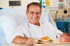 Male tålmodigt tyckande om mål i sjukhussäng Royaltyfri Foto