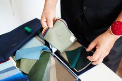 Male tailor choosing fabric. High angle close-up of male tailors hands searching through fabric samples for necessary one Royalty Free Stock Images