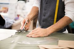 Male Tailor Cutting Fabric. Close up portrait of unrecognizable male tailor cutting fabric and making patterns for clothes while working in traditional atelier royalty free stock photos