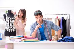 The male tailor with female student in workshop. Male tailor with female student in workshop Stock Photo