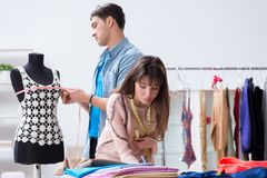 The male tailor with female student in workshop. Male tailor with female student in workshop Stock Image