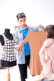 The male tailor with female student in workshop. Male tailor with female student in workshop Stock Photos