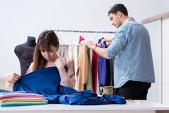 The male tailor with female student in workshop. Male tailor with female student in workshop Royalty Free Stock Images