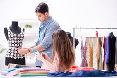 The male tailor with female student in workshop. Male tailor with female student in workshop Royalty Free Stock Photo