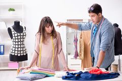 The male tailor with female student in workshop. Male tailor with female student in workshop Royalty Free Stock Image