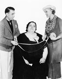Male tailor and his assistant measuring an overweight woman with a measuring tape Stock Photo