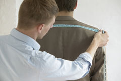 Male Tailor Measuring Customer's Suit. Rear view of young male tailor measuring customer's suit in fashion studio Royalty Free Stock Photos