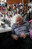 Male Tailor sews clothes in vintage workshop in Sofia, Bulgaria. September 9, 2015. People sew clothes. Repairing clothes on vintage sewing machine Royalty Free Stock Image