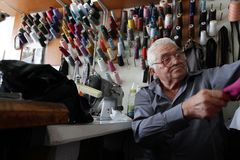 Male Tailor sews clothes in vintage workshop in Sofia, Bulgaria. September 9, 2015. People sew clothes. Repairing clothes on vintage sewing machine Royalty Free Stock Images