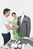 Male tailor taking measurement of suit while female coworker standing besides Royalty Free Stock Photo