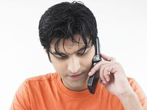 Male talking on his cell phone. Asian adult male talking on his cell phone Royalty Free Stock Images